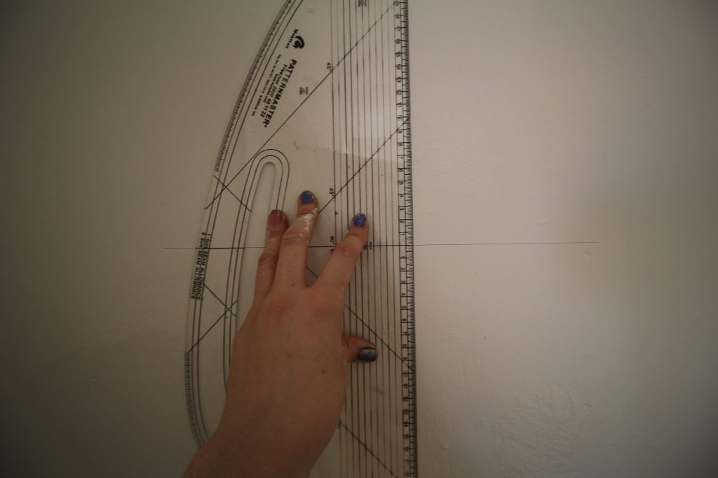 Draw a vertical line to line your first sheet of wallpaper up against