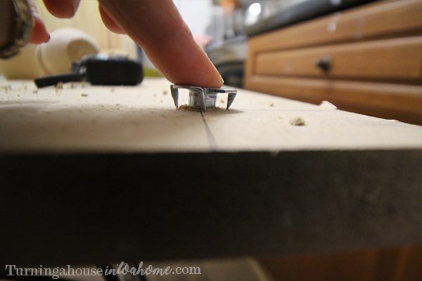Push the screw bit in and hammer it into the wood